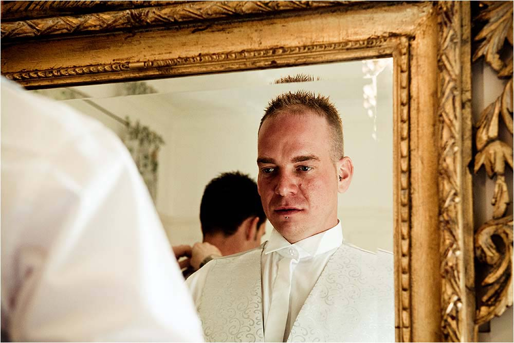 Bridegroom looking in a mirror while getting dressed