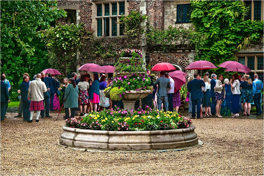 Guests sheltering under umbrellas in the courtyard