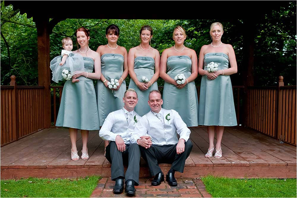 Adam and Ben with their five bridesmaids and a little flower girl
