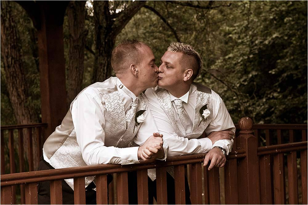 Adam and Ben kissing over a wooden railing
