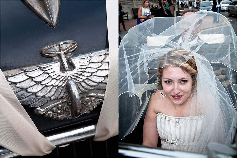 Bride sitting in the vintage wedding car with her veil blowing around her