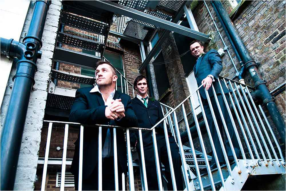 Gritty urban fashion style photograph of the groomsmen on a fire escape