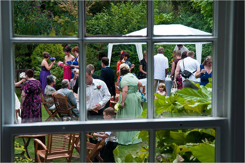 Guests having fun in the garden seen through a window