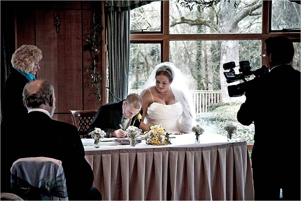 The couple sign the register while the videographer looks on