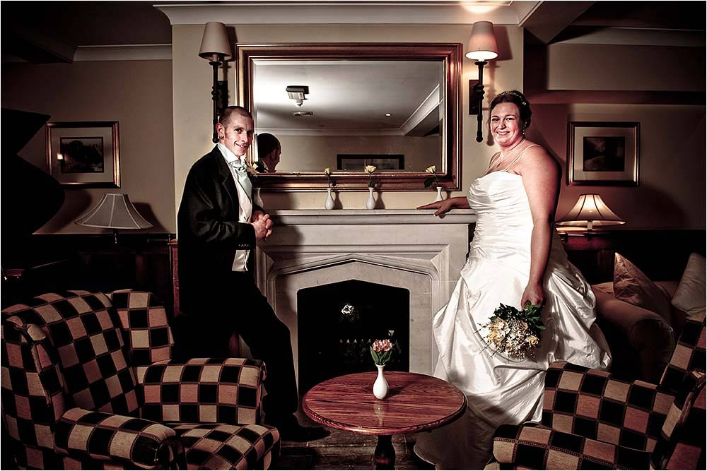Bride and Groom posing beside the fireplace in the restaurant
