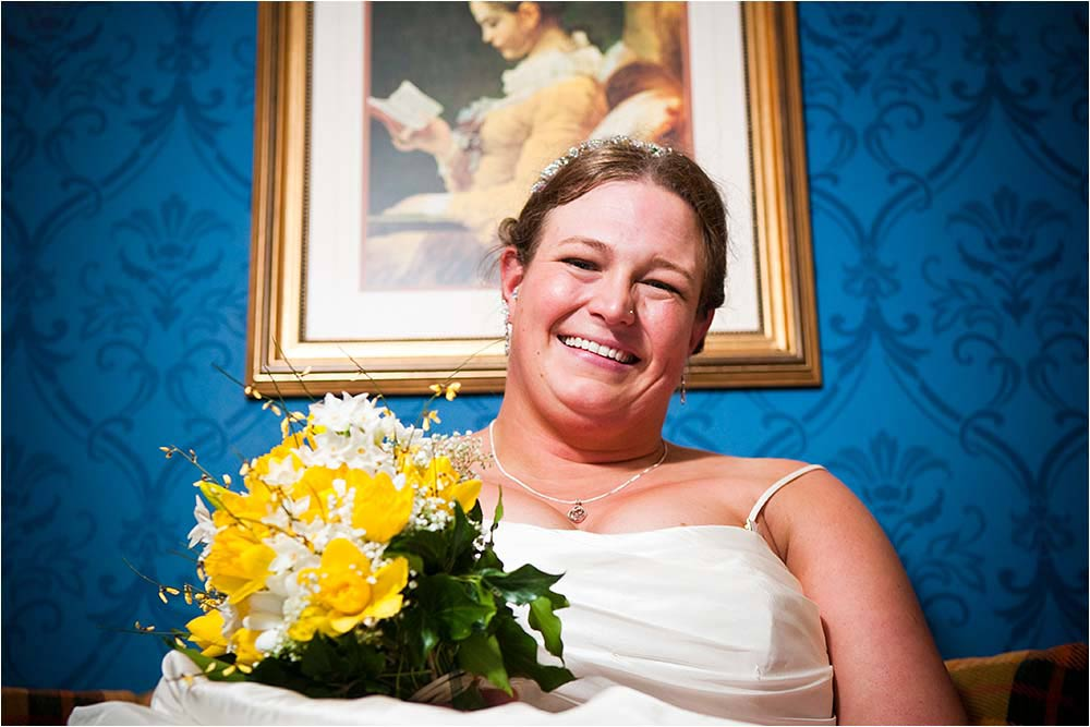 Smiling bride seen against a blue wallpaper background