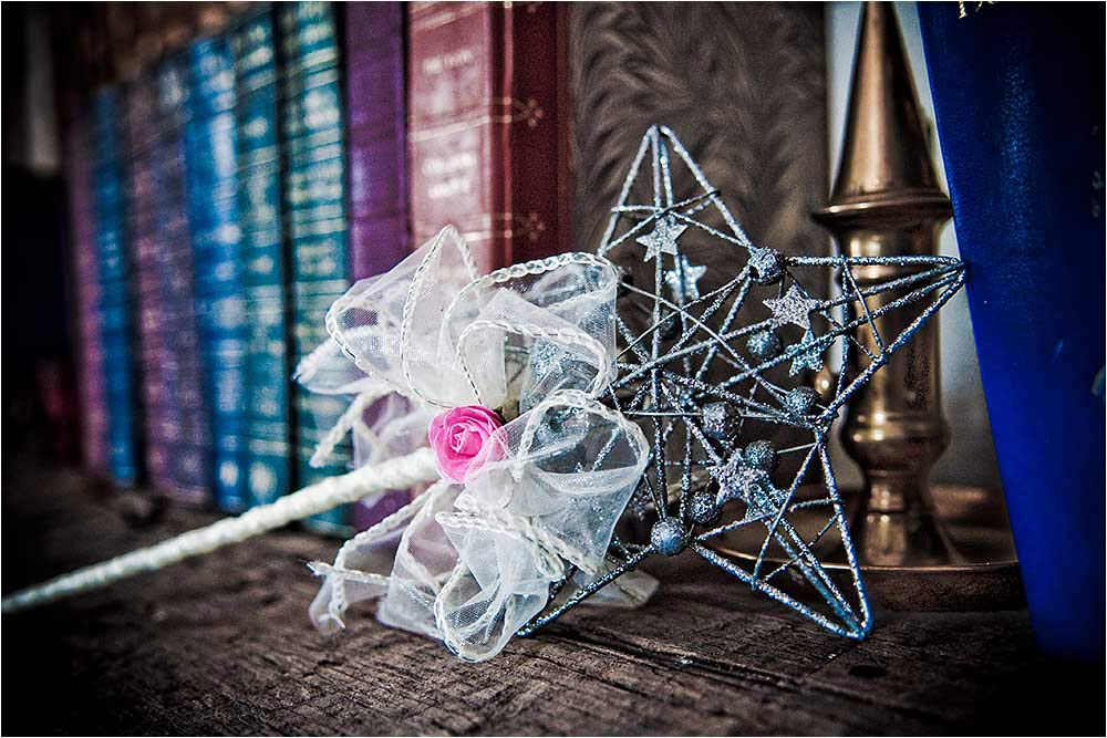 A fairy wand for the flower girl sitting on a wooden shelf with books behind