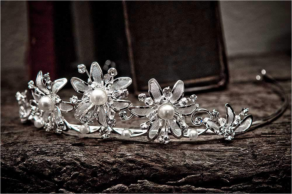 A metal flower tiara sitting on an old battered wooden shelf
