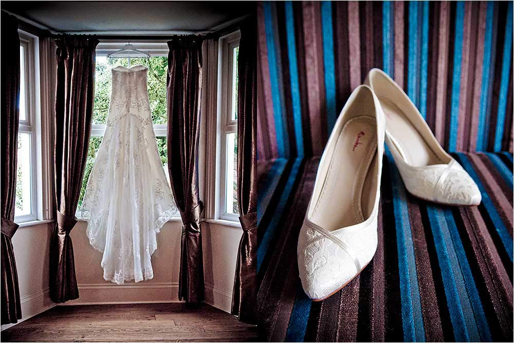 The wedding dress hanging in a window and the shoes sitting on a striped chair