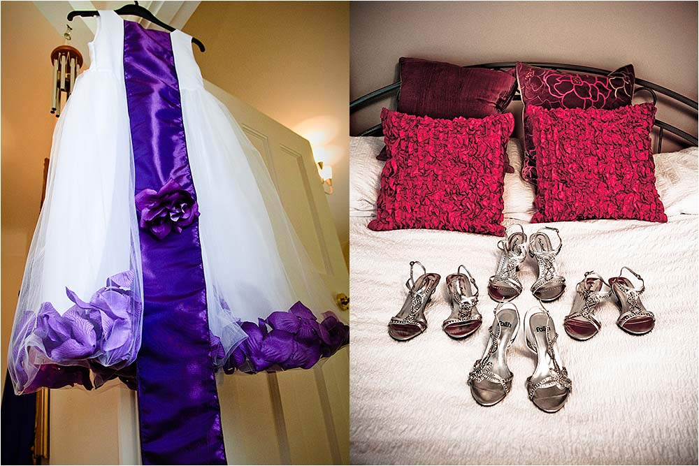 A bridesmaids dress hanging up and shoes on a bed