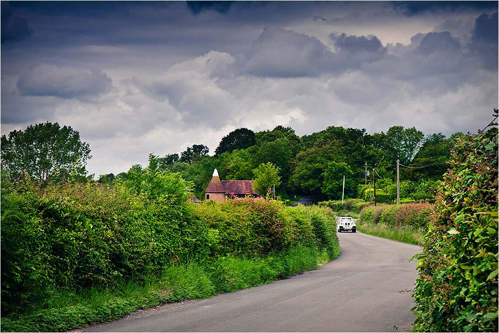 The vintage wedding ar seen coming down a country lane with storm clouds overhead
