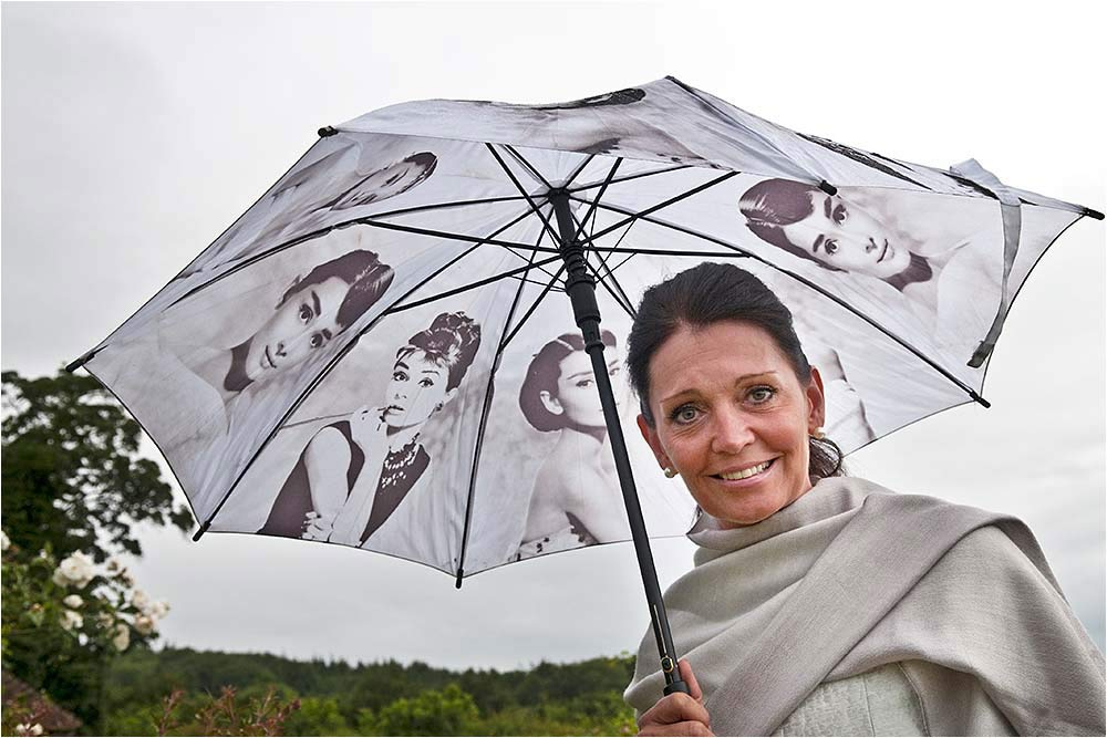 A woman standing under an Audrey Hepburn umbrella