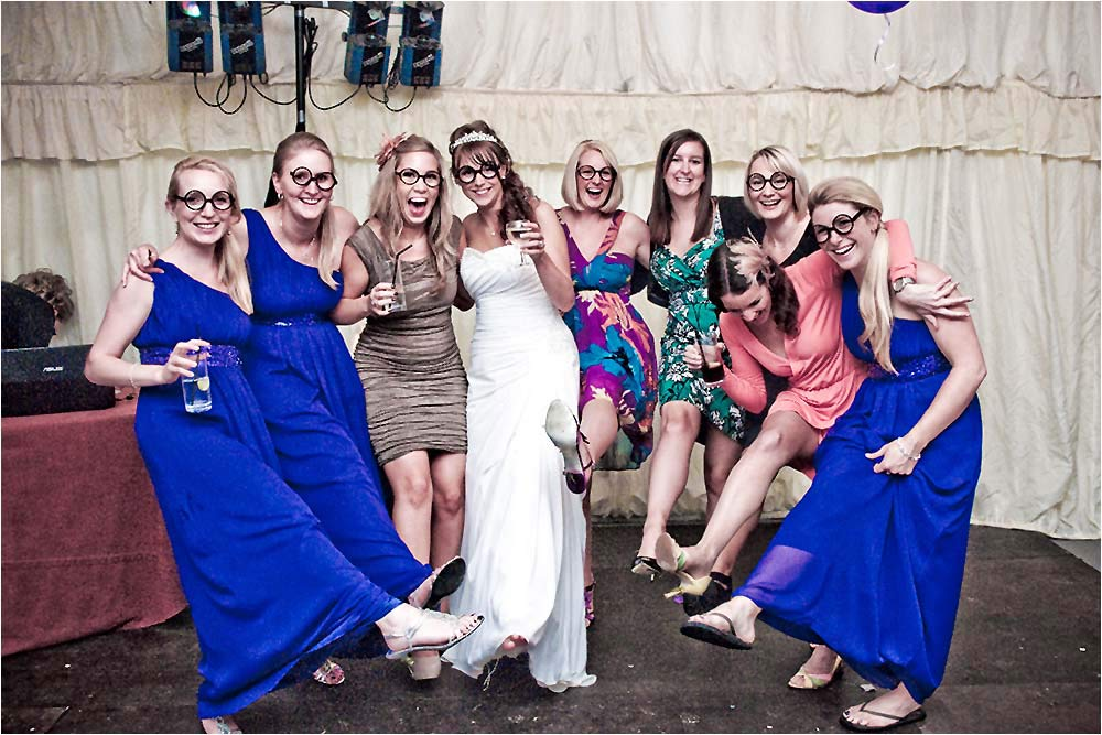 The hen party girls posing for a photograph wearing funny glasses