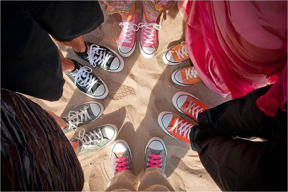 Guests feet in converse trainers on a sandy beach