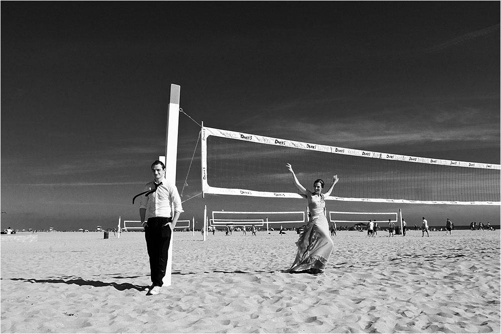 Posing with the volleyball net at Huntington Beach in black and white