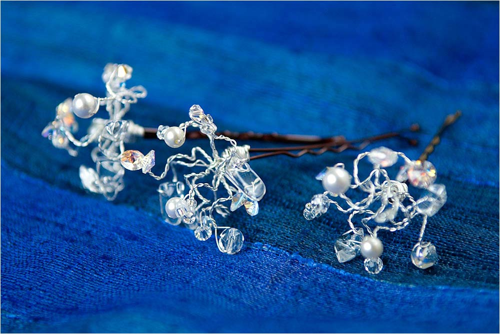 Faux diamond and pearl beaded hair grips on a blue cloth
