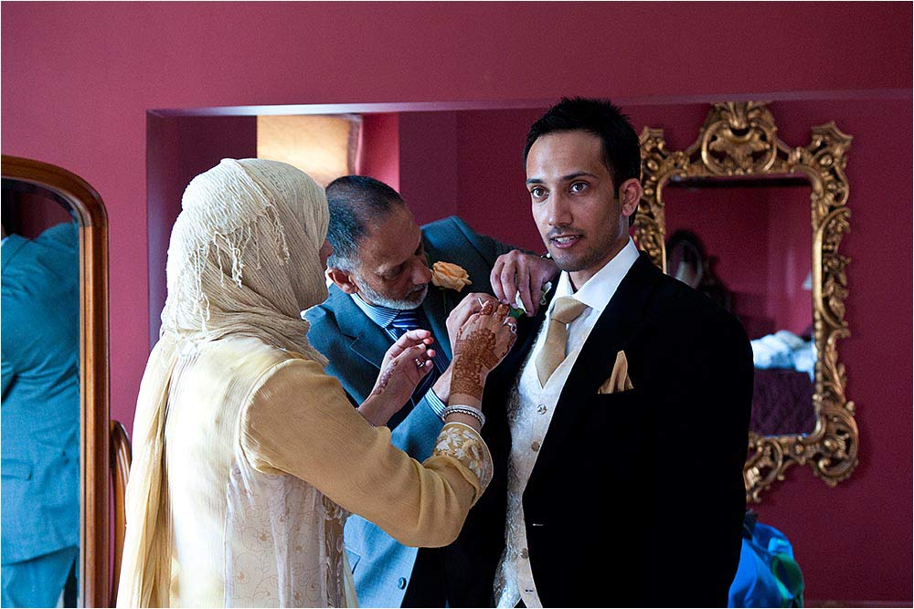 The groom getting changed into a suit assisted by his parents