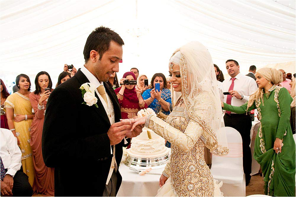 The bridegroom putting the ring onto his brides finger