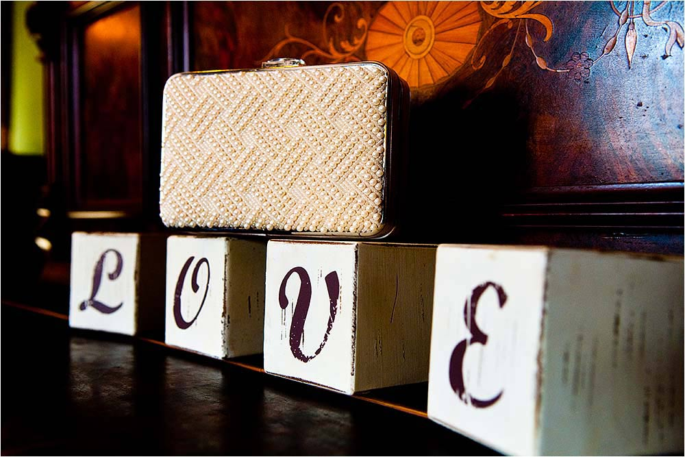 A small beaded clutch bag sitting on wooden blocks spelling the word love