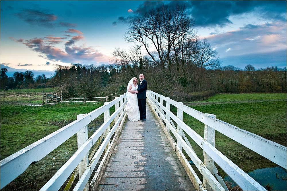 Bride and groom standing together on Alfriston Bridge over the River Cuckmere