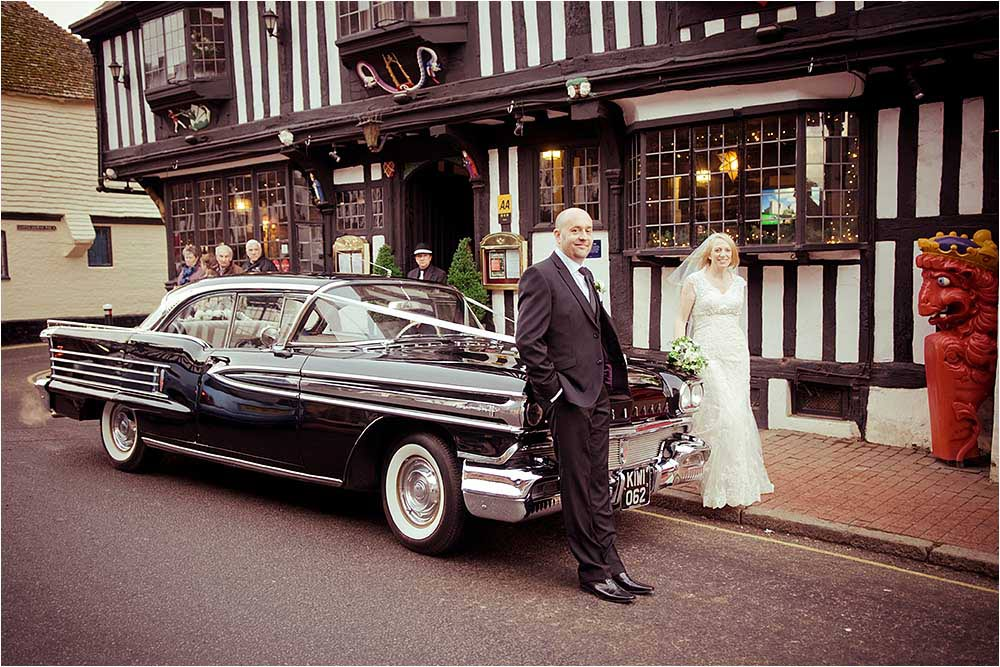 Bride and groom stnading in front of the wedding car outside the Star in Alfriston