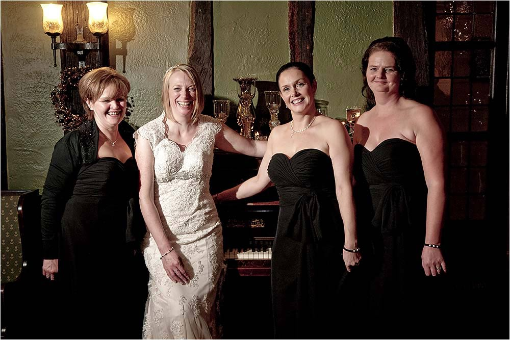 Lisa standing beside a piano in the library with her bridesmaids