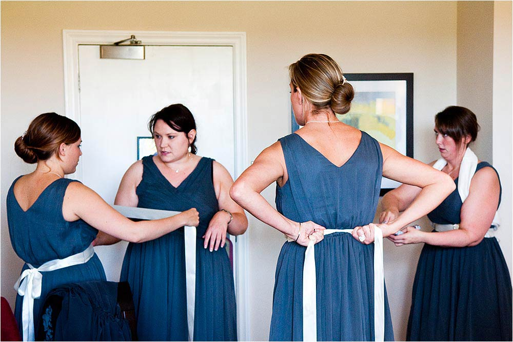 Bridesmaids tieing ribbons onto their blue dresses