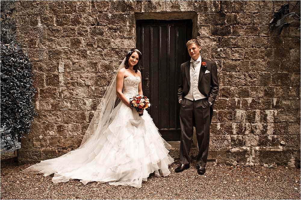 Bride and groom standing by the stone wall of an old barn