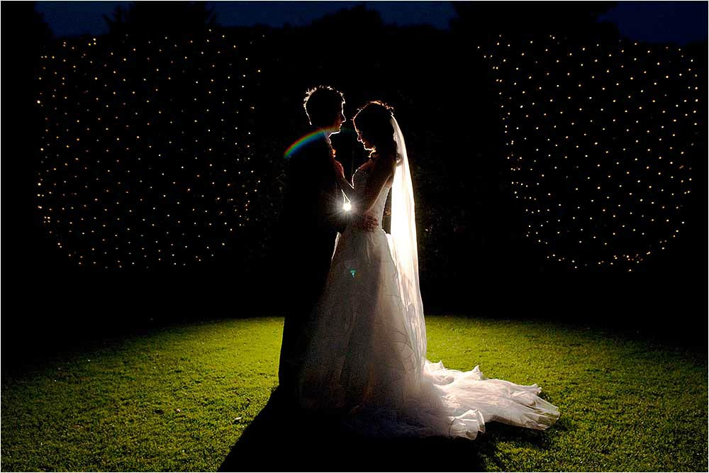 A rainbow around the bride and groom caused by lense flare from a remote strobe